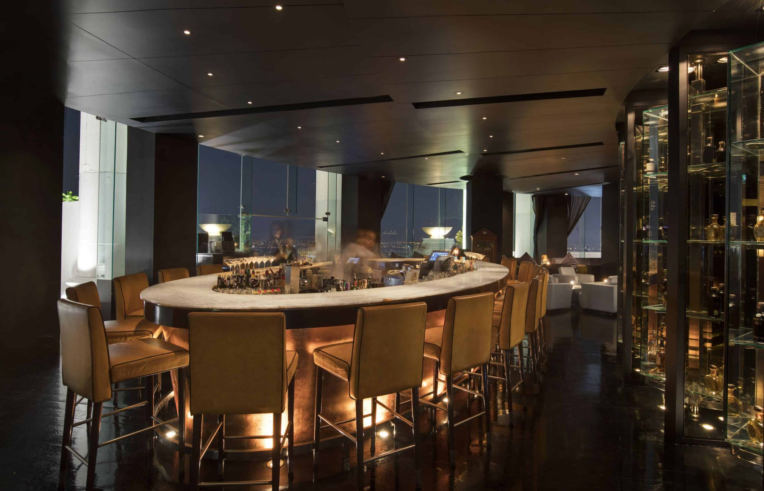 rish shaped bar with aligned stools and high grey ceiling