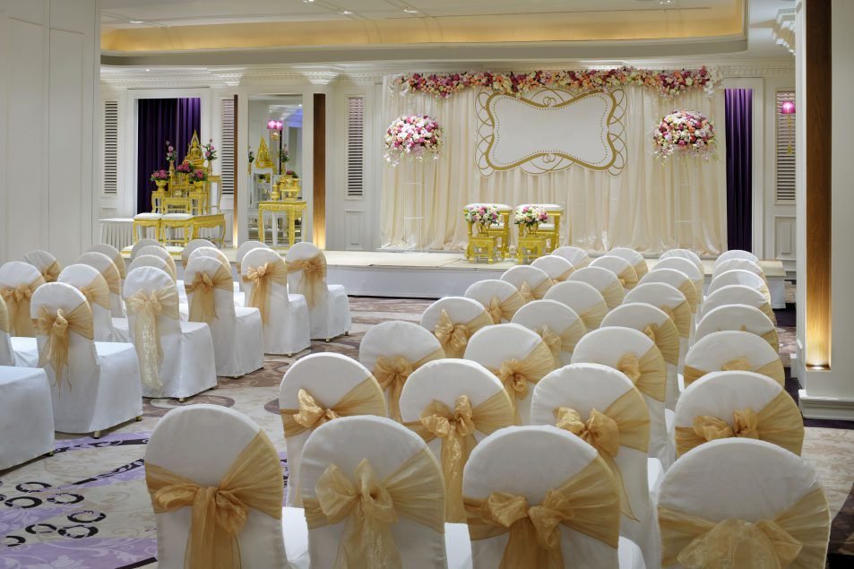 wedding venue aligned white chairs with bow in front of alter