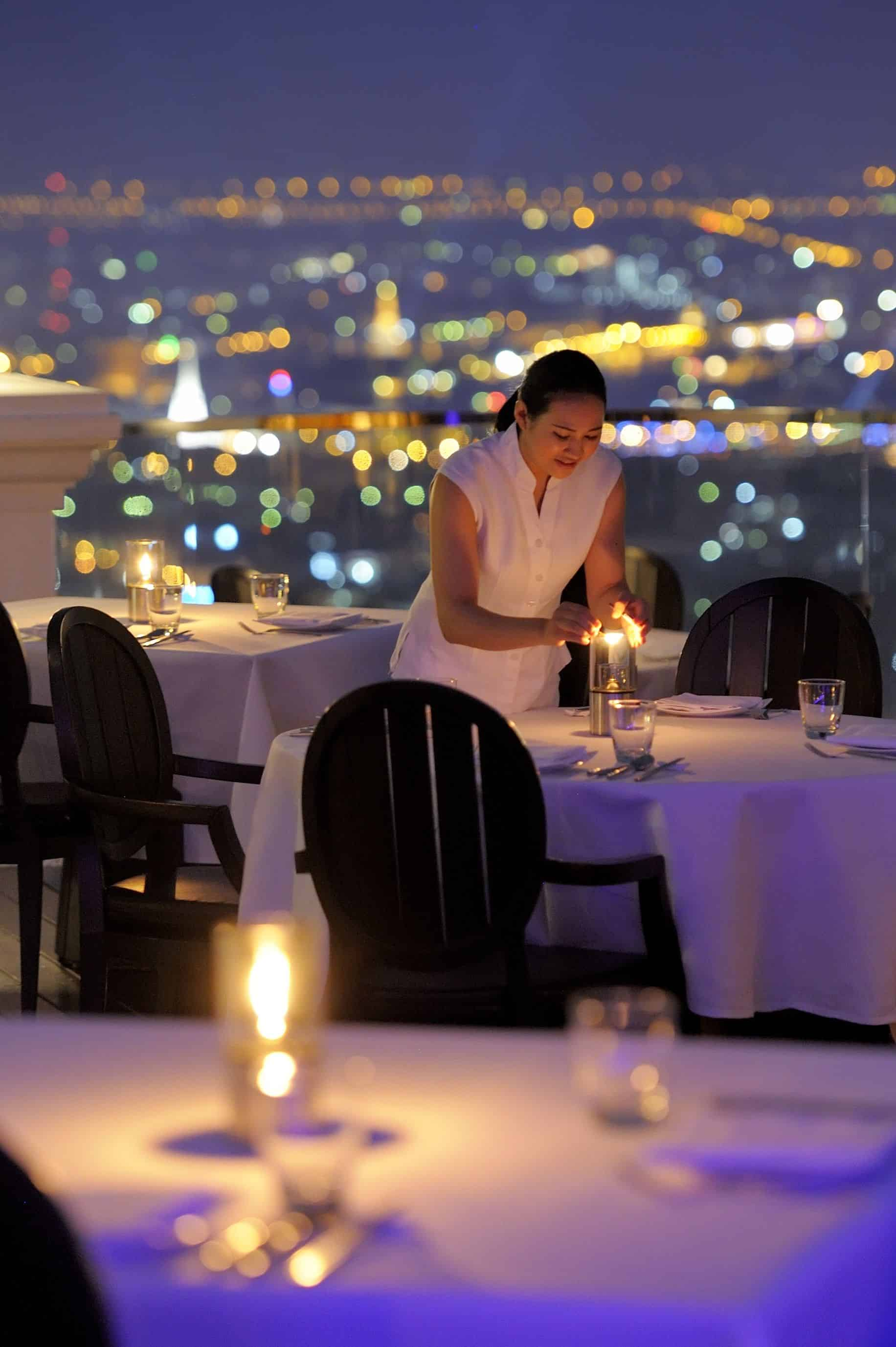 woman in white dress lighting candles on terrace table