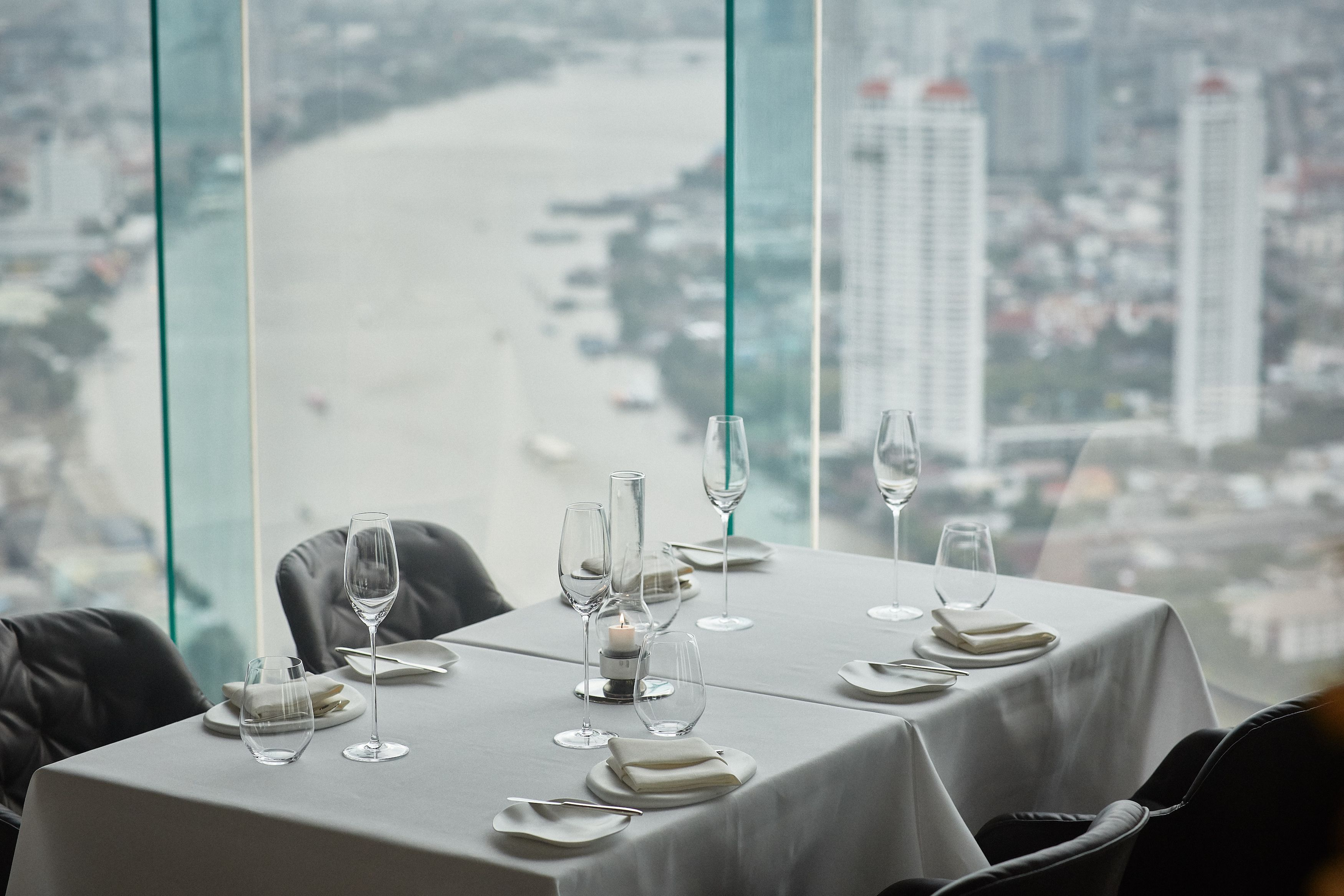 restaurant table by window set with white linens with silver wear and glasses grey chairs