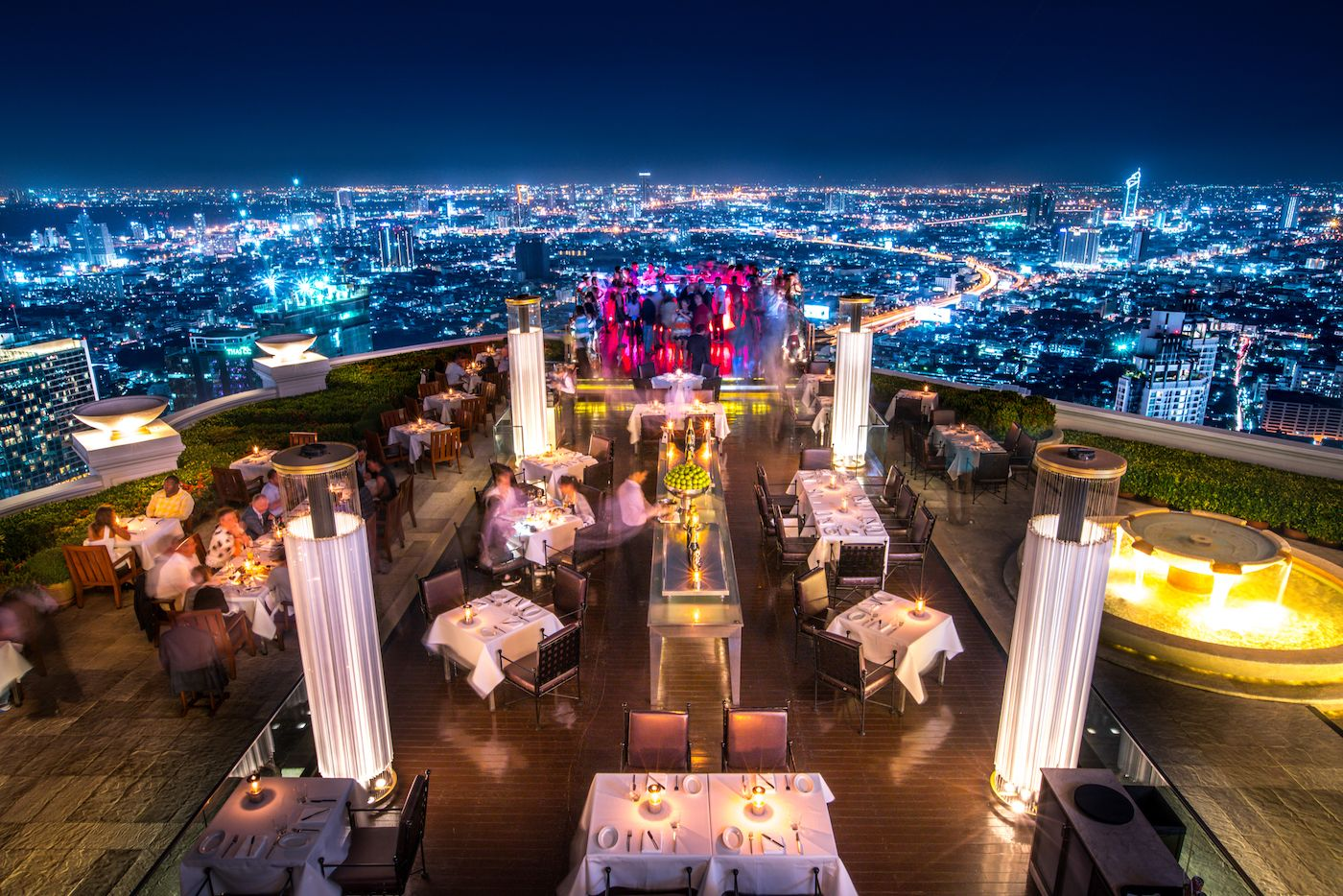 aerial view of restaurant terrace with heaters and city in the background