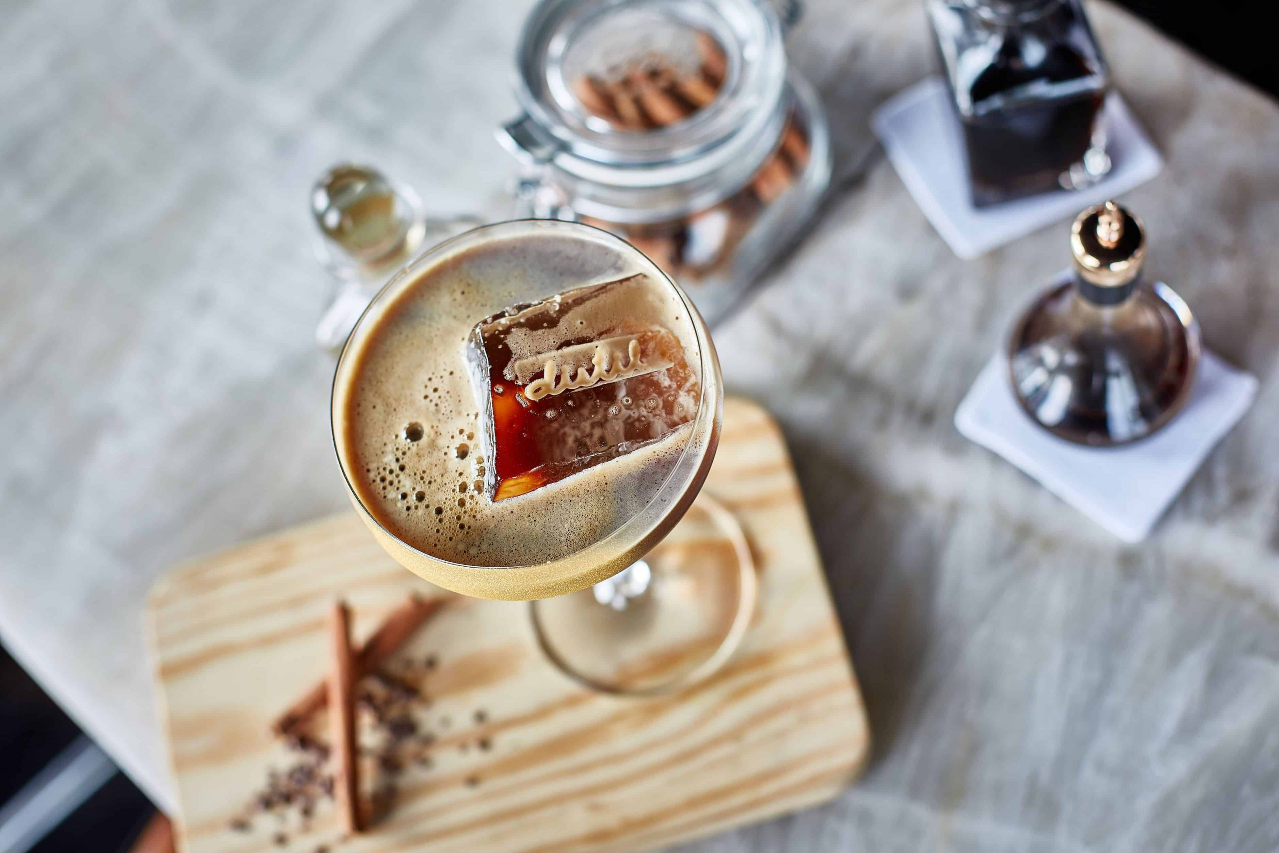 cocktail with ice cube on wooden board with cinnamon