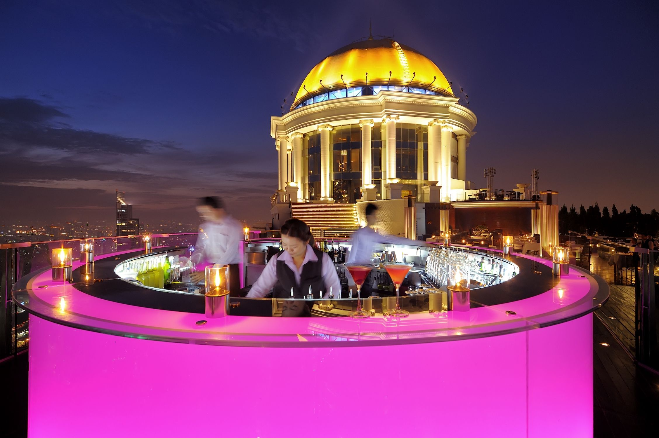 pink light bar by edge of terrace and yellow dome in background