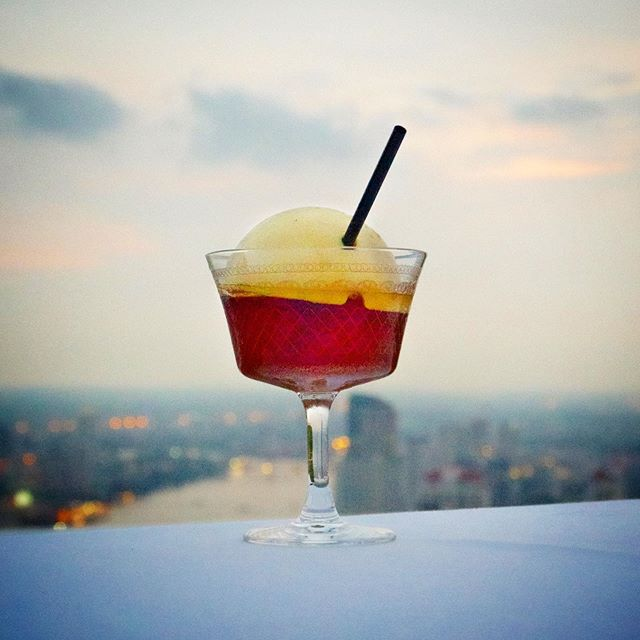 Orange cocktail with city in background
