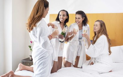 Small group celebrating with champagne on a bed within a Tower Club suite