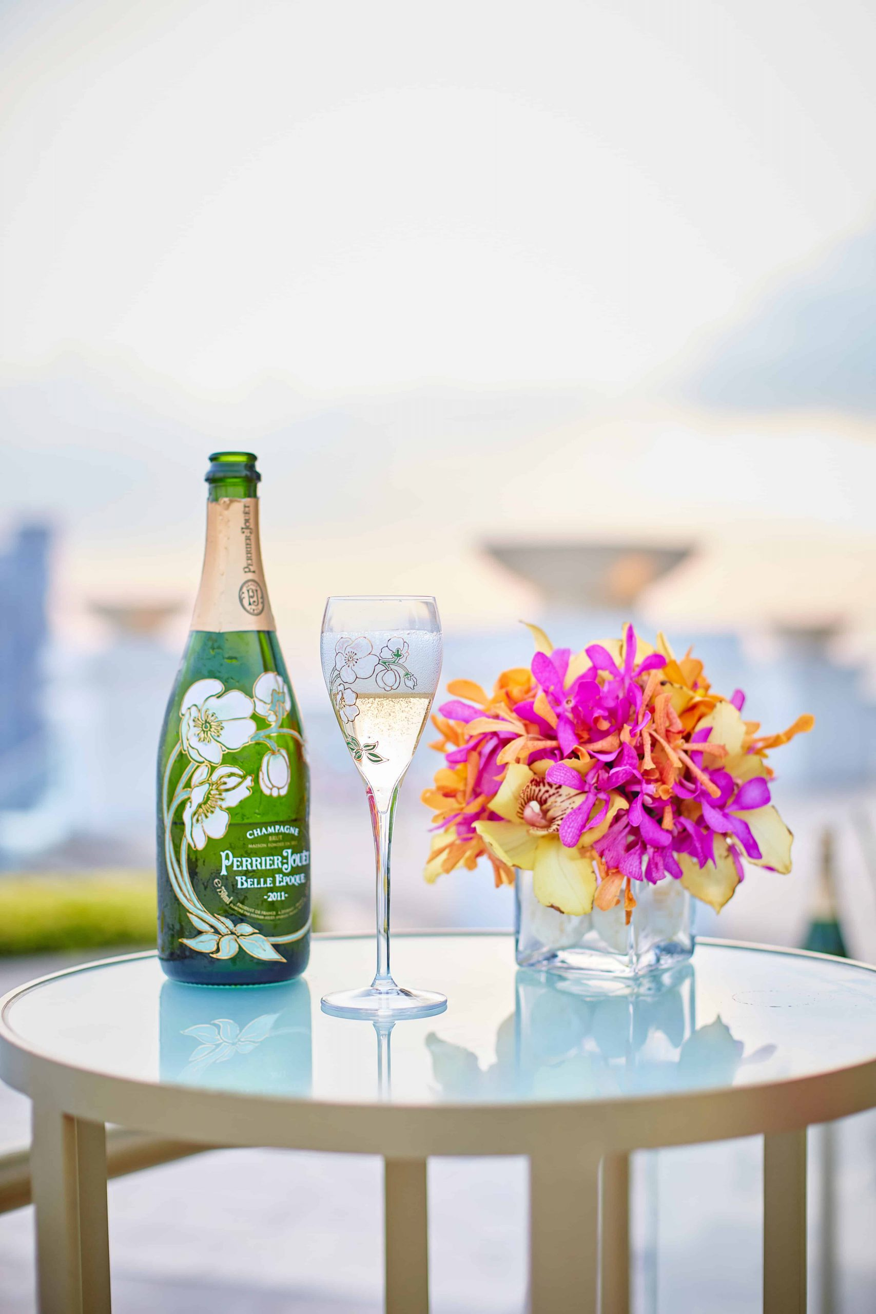 Bottle of wine with a glass of win and flowers