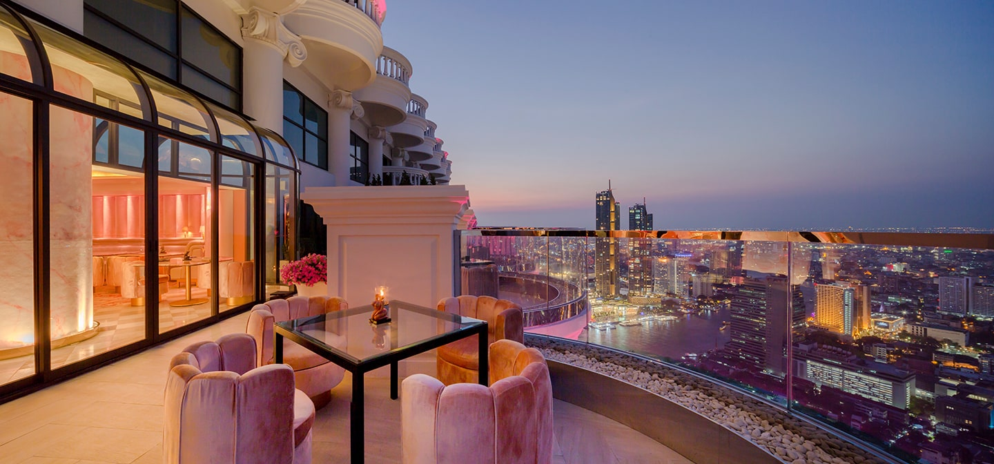 rooftop balcony pink chairs around glass table city skyline view