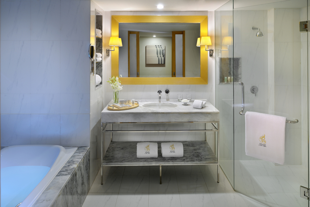 bathroom with centered mirror and marble sink bathtub on left side and shower on right side