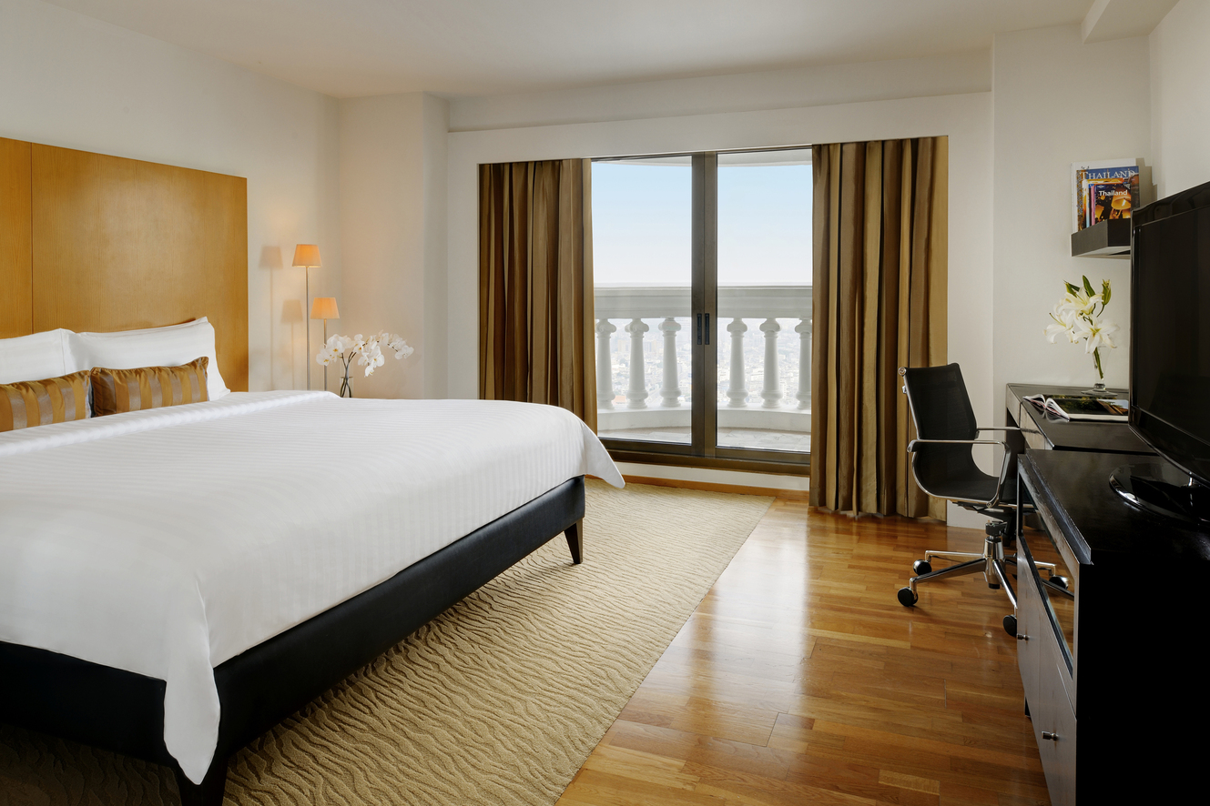 Hotel suite with king size bed, window and office chair