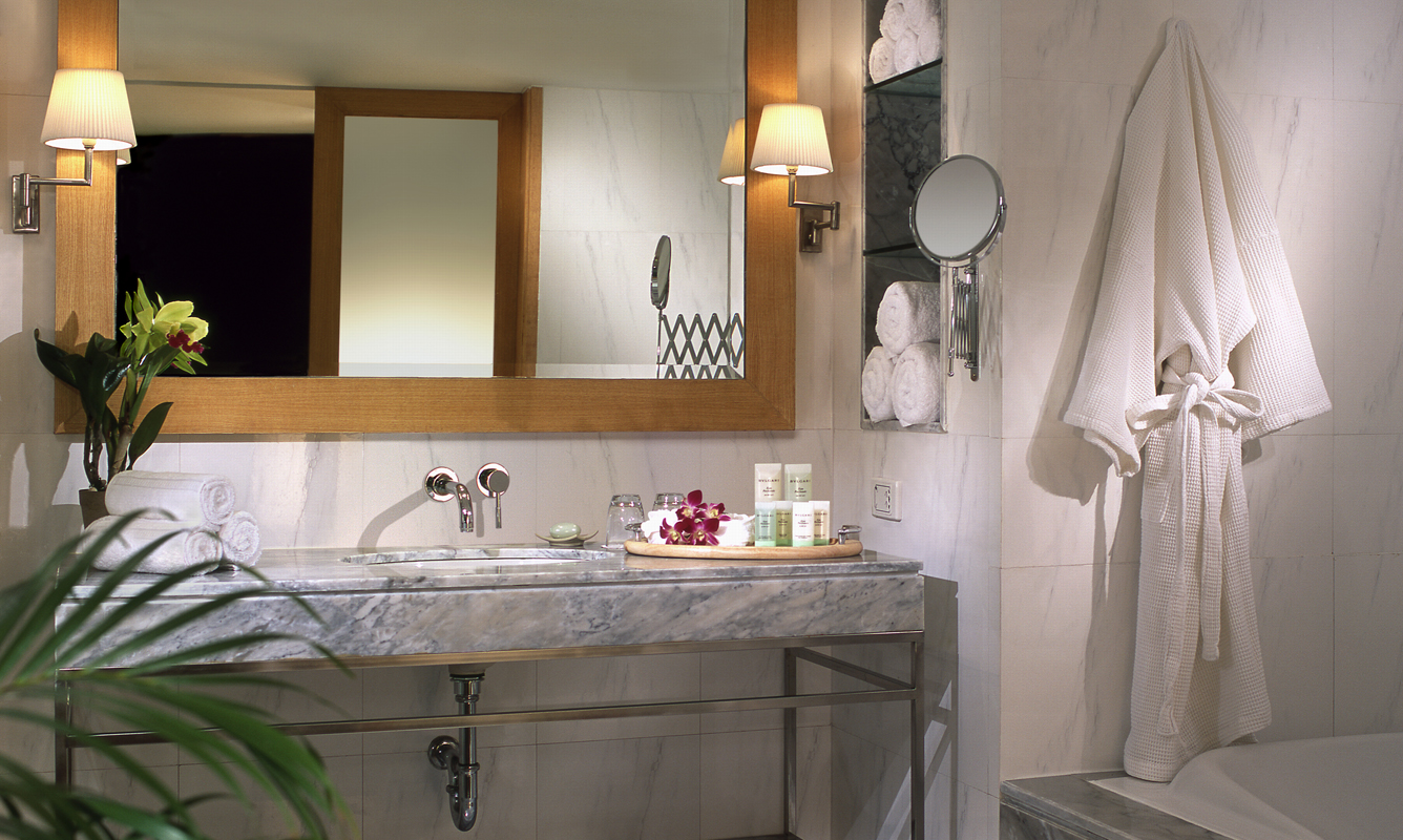 bathroom with marble sink mirror and white bathrobe