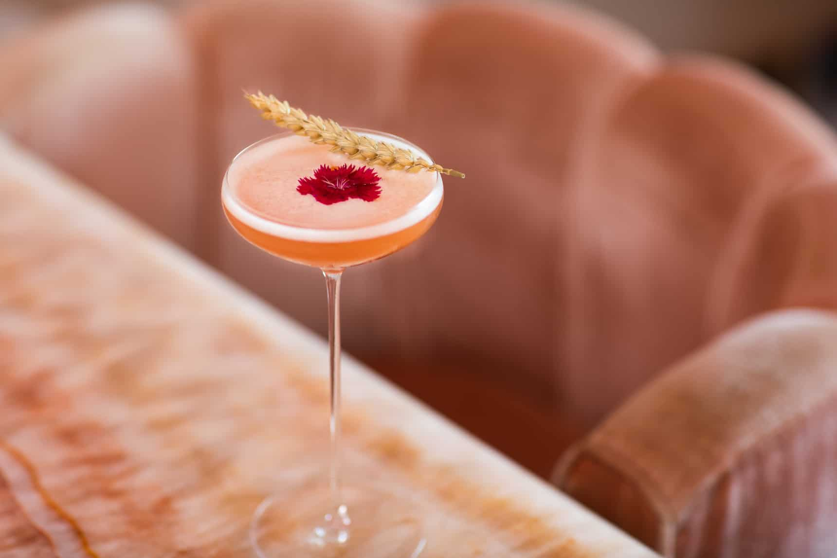 pink cocktail wheat garnish on table