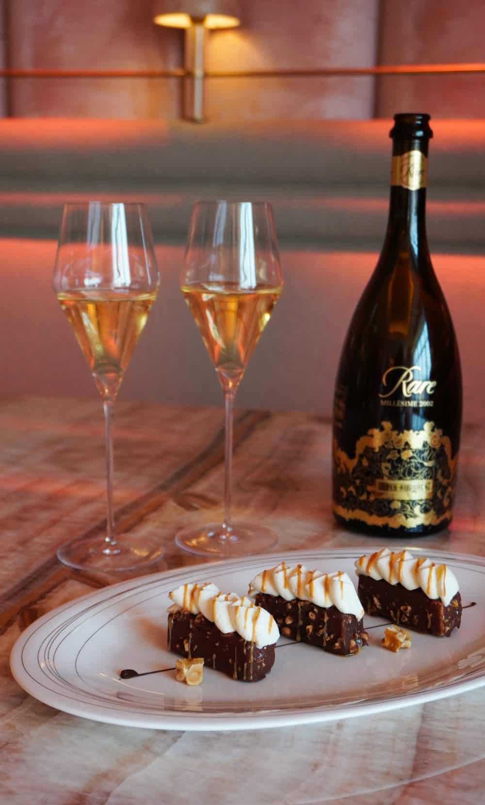 champagne flutes and bottle next to 3 pieces of chocolate dessert