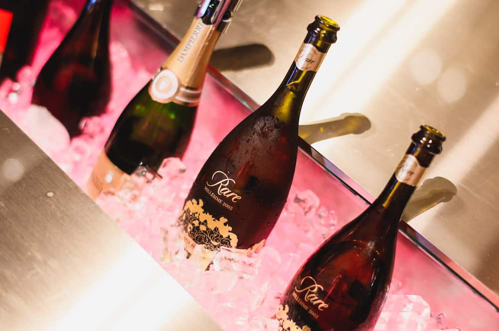 row of champagne bottles chilled in ice