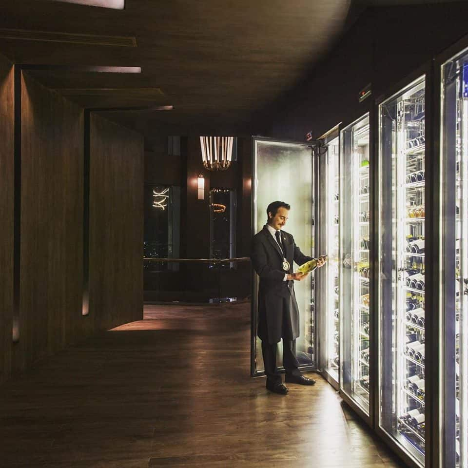 sommelier looking at his collection of wine bottles