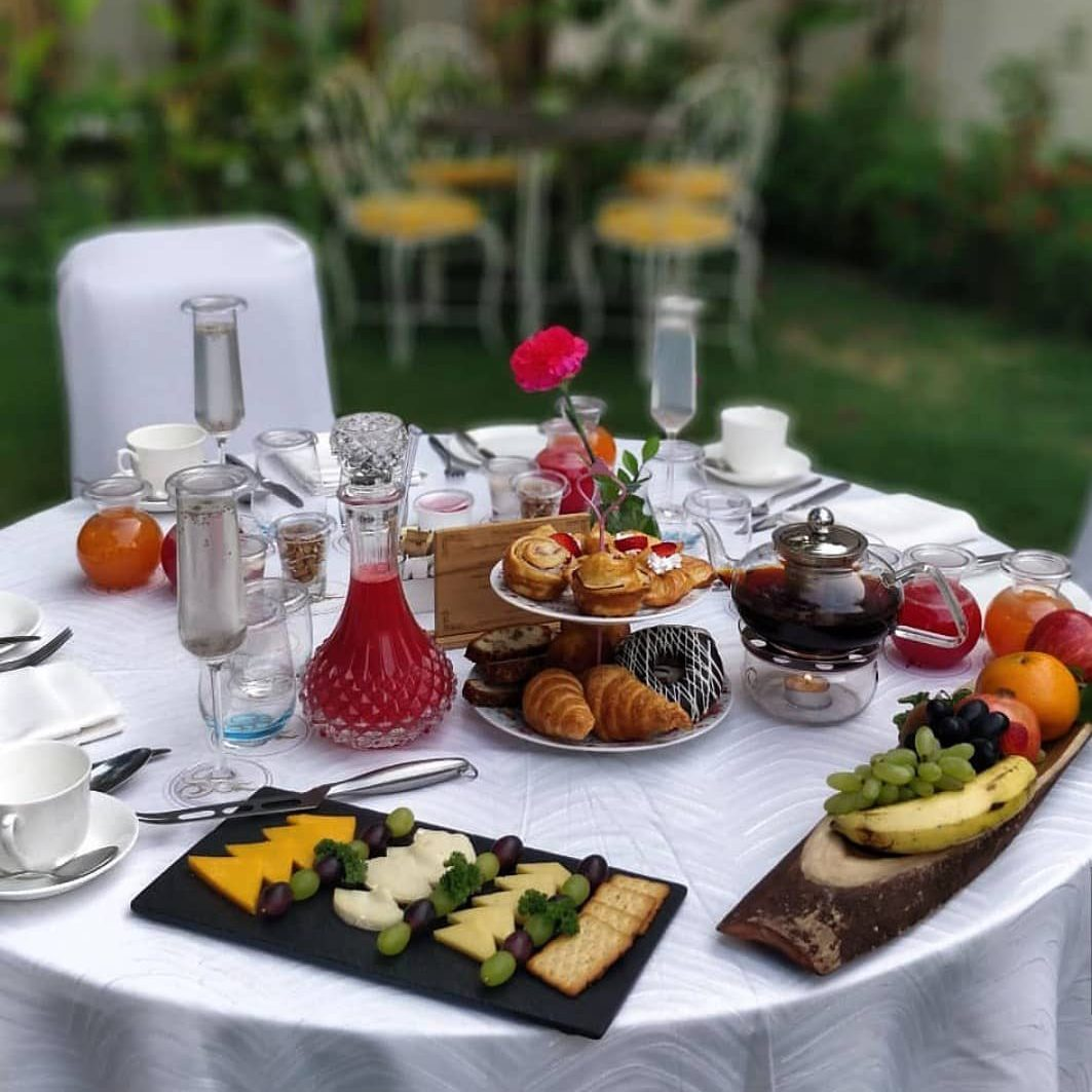 A breakfast on a white table in a garden