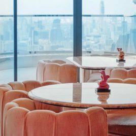 pink tables and seats facing Bangkok views