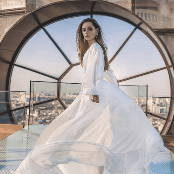 Woman wearing a white dress standing on a rooftop