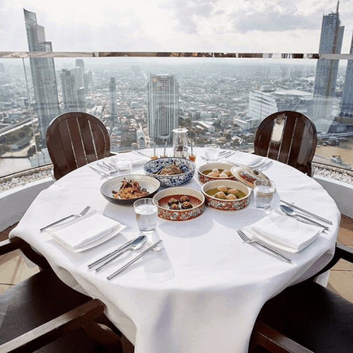 A white table on a rooftop with Bangkok views